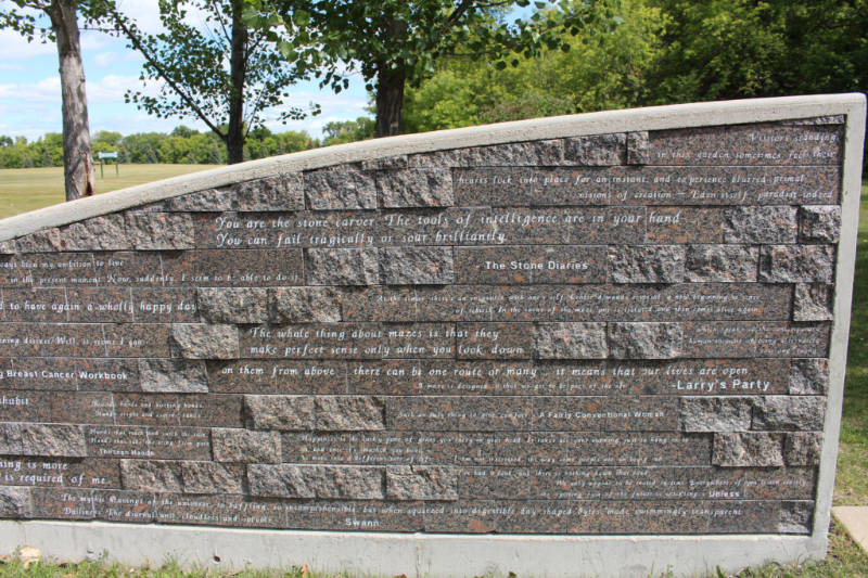 A stone wall with Carol Shields quotes written on it at the Carol Shields Memorial Labyrinth