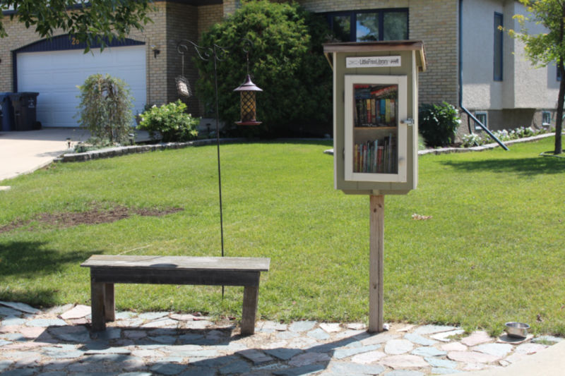 A Little Free Library with a bench to sit on beside it
