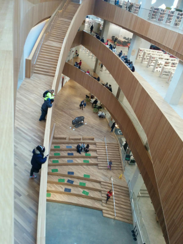 Several stories open to a flowing staircase and the lobby below at the Calgary Central Library