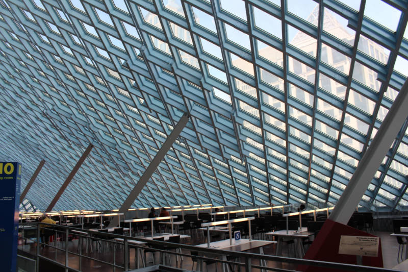 Steel paned window form a wall and a ceiling on one of the interior levels of the Seattle Central Library