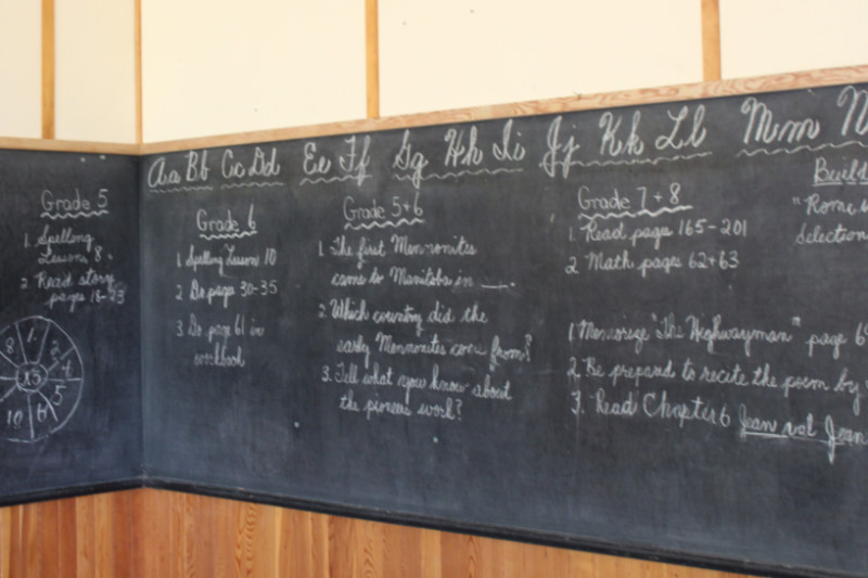 Chalkboard in schoolroom with letters and assignments written in white chalk on it