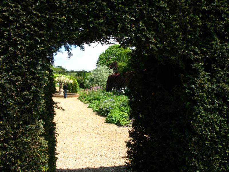 A greenery framed door looking into a garden